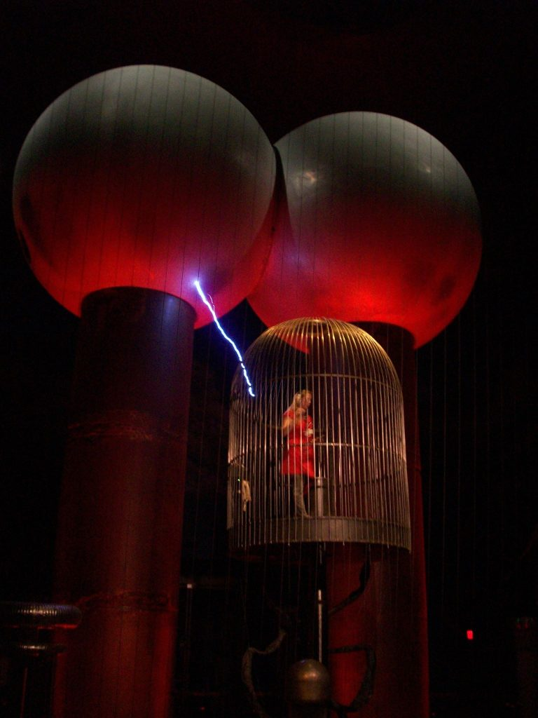 A giant Van der Graaff generator at the Boston Museum of Science creates lightning bolts, zapping a cage containing the show's presenter