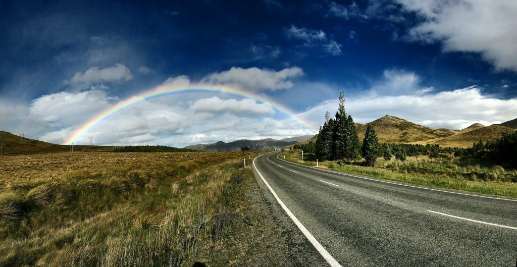 A rainbow arches over a country road after rain